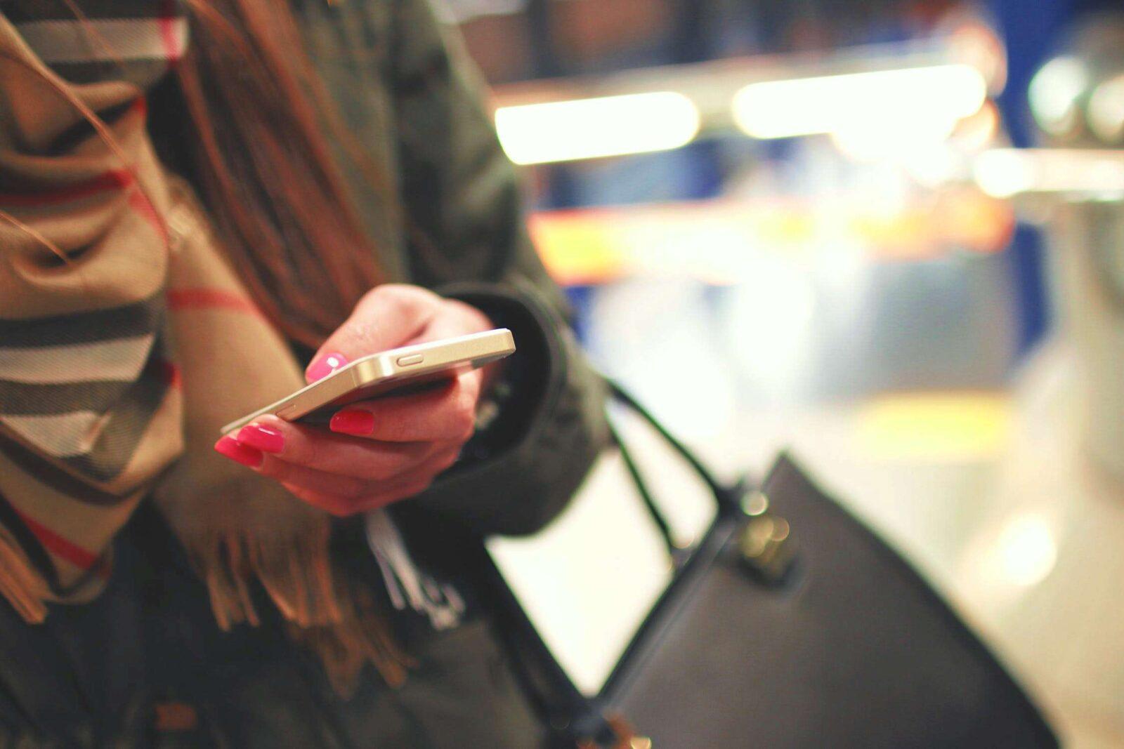 kobieta komórka manicure paznokcie różowe tipsy torba komunikacja miejska