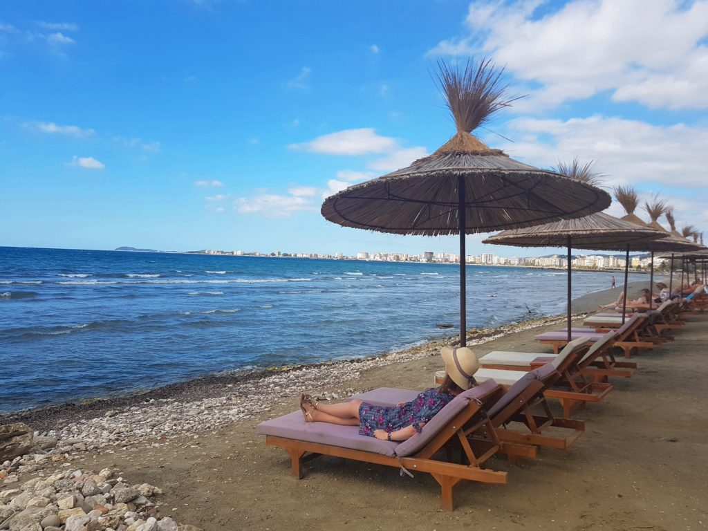 Plaża-woda-morze-Albania-leżak-parasole-kapelusz-kobieta-niebo-chrześcijanka-z-sąsiedztwa
